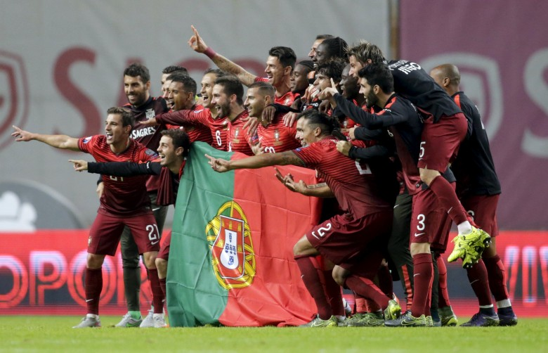 Portugal's team poses with the flag of Portugal at the end their Euro 2016 qualifying soccer match against Denmark at Municipal Stadium in Braga
